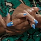 Fashion designer Tracy Reese clasps her hands with blue and white patterned-painted nails, during a backstage interview before presenting Spring 2013 collection in New York. (AP Photo/Bebeto Matthews)