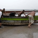 People remove a boat from the water ahead of the arrival of Hurricane Sandy in Manzanillo, Cuba