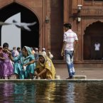 Indian Muslim women wash themselves near a fountain as a pigeon flies by at the Jama Masjid, or the Grand Mosque, in New Delhi, India. The Jama Masjid is one of India's biggest mosques. (AP Photo/Altaf Qadri)