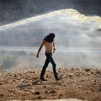 A Palestinian protester walks away from a water canon used by Israeli troops to disperse protesters during a weekly protest against the expansion of the nearby Jewish settlement of Halamish, in the West Bank village of Nabi Saleh near Ramallah. (AP Photo/Majdi Mohammed)