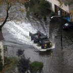 An emergency vehicle drives on a flooded street in Little Ferry, NJ in the wake of superstorm Sandy on Tuesday. 