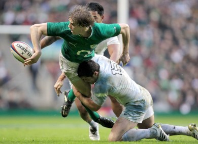 Andrew Trimble offloads in the tackle against England.