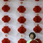 A woman holds a folding fan near a decoration in Beijing. (AP Photo/Lee Jin-man)
