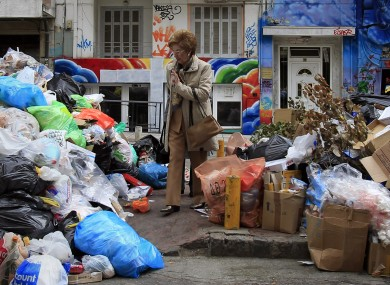 A woman passes by piles of garbage amassed during succesive strikes by municipal workers in the Greek city of Thessaloniki.
