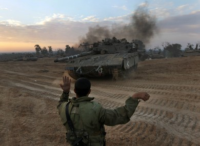 An Israeli soldier guides a tank to a new position at a staging area near the Israel Gaza Strip Border, southern Israel yesterday.