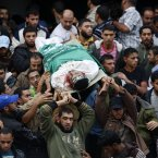 Palestinians carry the body of Ali Al-Mana'ama, a Hamas militant, during funeral in Maghazi Refugee Camp, central Gaza Strip, today. A group of Hamas militants was killed in an Israeli air strike east of Maghazi Refugee Camp early Saturday morning, Palestinian officials said.(AP Photo/Adel Hana)