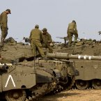 Israeli soldiers work on their a tanks in a staging ground near the border with Gaza Strip, southern Israel, Saturday, Nov. 17, 2012. Fierce clashes between Israeli forces and Gaza militants are continuing for the fourth day. (AP Photo/Ariel Schalit)