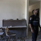 An Israeli police officer stands inside a damaged house after a rocket fired by Palestinian militants from Gaza Strip landed in Ashkelon, southern Israel, today. 