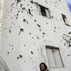 A woman stands next to a damaged house after a rocket fired by Palestinian militants from Gaza Strip landed in Ashkelon, southern Israel today. 