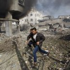 Palestinians run away from a damaged building after an Israeli air strike in Gaza City, today. 