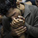 A Palestinian man kisses the hand of a dead relative in the morgue of Shifa Hospital in Gaza City, today. 