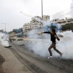 A Palestinian throws back a tear gas canister during a protest against Israel's operations in Gaza Strip, outside Ofer, an Israeli military prison near the West Bank city of Ramallah, today. (AP Photo/Majdi Mohammed)
