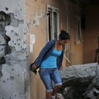 A woman walks outside a damaged house after a rocket fired by Palestinian militants from inside the Gaza Strip, landed at the community of Ofakim, in southern Israel, today.