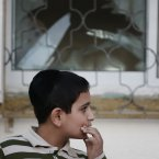 A child looks at damages of a house after a rocket fired by Palestinian militants from inside the Gaza Strip, landed at the community of Ofakim, in southern Israel, Sunday, 18 November. (AP Photo/Lefteris Pitarakis)