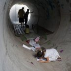 Israelis hide in a concrete tube during a rocket attack from Gaza, in Nitzan, southern Israel.