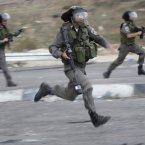 Israeli border policemen run during a protest against the Israeli military operations in Gaza Strip near the West Bank city of Nablus. 
