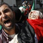A Palestinian man holds the body of 11-month-old Ibrahim Daloo during a funeral for members of the Daloo family in Gaza City. 