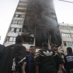 People stand in front of a high rise housing media organizations in Gaza City, Monday.