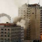 Smoke and fire are seen from an explosion by a high rise housing media organizations in Gaza City.