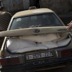 Palestinians jump into a car after collecting bags of flour at a UN distribution center in Shati refugee camp, Gaza City. 