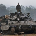 An Israeli soldier stands on a tank at a staging area near the Israel Gaza Strip Border. (AP Photo/Lefteris Pitarakis)