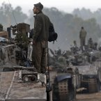 An Israeli soldier looks on atop of a tank at a staging area near the Israel Gaza Strip Border. (AP Photo/Lefteris Pitarakis)
