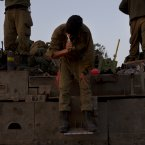 An Israeli soldier brushes his teeth while standing on an armored personal carrier in a staging area near the Israel Gaza Border, southern Israel earlier today. (AP Photo/Ariel Schalit)