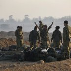An Israeli soldier among comrades stretches after he woke up at a staging area near the Israel Gaza Strip Border, southern Israel, early Tuesday. (AP Photo/Lefteris Pitarakis)