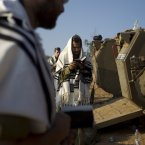 Israeli soldiers read from a holy book as they pray next to armored personal carriers in a staging area near the Israel Gaza Border. (AP Photo/Ariel Schalit)