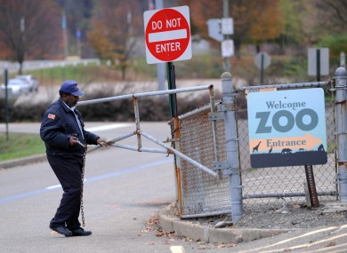 A security guard closes the gate at the Pittsburgh Zoo yesterday