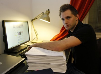 Max Schrems sits with files about his activities on his Facebook account that Facebook handed over to him last year.