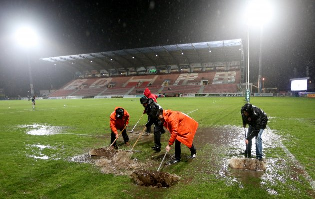 Groundsmen remove water from the pitch 14/12/2012