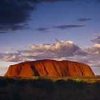 Giant red rock formation at dusk overshadowed by storm clouds at Ayers Rock (Eye Ubiquitous/Press Association Images)