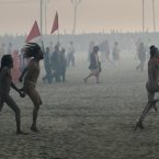 Naked Hindu holy men or a Naga Sadhus run towards  Sangam. (AP Photo /Manish Swarup)