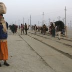 An Indian Hindu holy man, or Sadhu, holds his bag on his head as he arrives at Sangam. (AP Photo/Kevin Frayer)