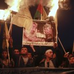 Palestinians hold torches and posters of late Palestinian President Yasser Arafat and late Hamas founder and spiritual leader Sheik Ahmed Yassin, during a rally marking the 48th anniversary of the Fatah movement in Gaza City. The Arabic on poster reads: Rest in peace in heaven our late leaders. (AP Photo/Adel Hana)
