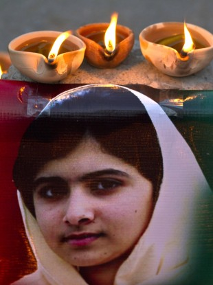 Clay lamps burn near a poster of 15-year-old Malala Yousufzai in Islamabad.