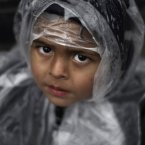 A Pakistani boy warped with a plastic sheet to shield the rain, looks up while standing with his father, not seen, a supporter of Pakistani Sunni cleric Tahir-ul-Qadri, during an anti-government rally in Islamabad, Pakistan, Thursday, Jan. 17, 2013. Qadri is demanding the government be dissolved and replaced with a caretaker administration formed in consultation with the judiciary and the military. He also wants electoral reform to weed out corrupt politicians and prevent them from winning elections in the future. (AP Photo/Muhammed Muheisen)