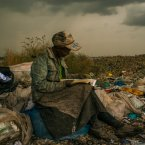 Pausing in the rain, a woman working as a trash picker at the 30-acre dump wishes she had more time to look at the books she comes across. (Image: Micah Albert)