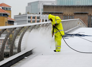 A worker uses a high temperature pressure washer to remove chewing gum and clean the Millennium Bridge in London, on the last day of it's annual clean and maintenance.