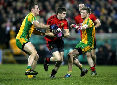 Connaire Harrison of Down is tackled by Neil McGee of Donegal.