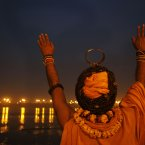 A Sadhu, or Hindu holy man, performs evening rituals at Sangam, the confluence of the rivers Ganges, Yamuna and mythical Saraswati during the Maha Kumbh Mela in Allahabad, India. Millions of Hindu pilgrims are expected to attend the Maha Kumbh festival, which is one of the world's largest religious gatherings that lasts 55 days and falls every 12 years. During the festival pilgrims bathe in the holy Ganges River in a ritual they believe can wash away their sins. (AP Photo/Rajesh Kumar Singh)