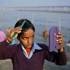 A young Indian Hindu devotee combs his hair after a dip at the Sangam, the confluence of the Ganges, Yamuna and mythical Saraswati River, during the Maha Kumbh festival in Allahabad, India, Thursday, Feb. 21, 2013. Millions of Hindu pilgrims have been attending the Maha Kumbh festival, which is one of the world's largest religious gatherings that lasts 55 days and falls every 12 years. (AP Photo/ Rajesh Kumar Singh)