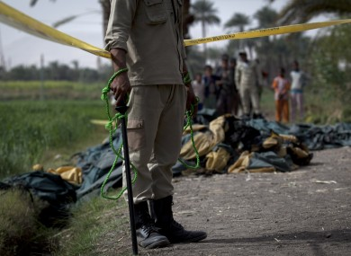 An Egyptian policeman stands guard at the side of the balloon accident