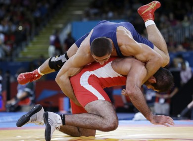 Kurban Kurbanov of Uzbekistan, in red, and George Gogshelidze of Georgia wrestle at London 2012.