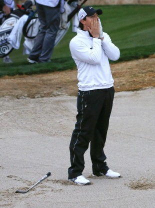 Rory McIlroy reacts after hitting out of the bunker onto the 18th green.