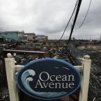 A sign for Ocean Avenue stands in the smoldering ruins of houses in the Breezy Point section of New York, Tuesday, Oct. 30, 2012. (AP Photo/Mark Lennihan)