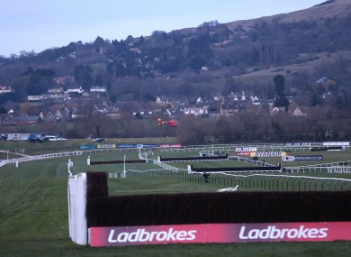 An air ambulance carrying jockey JT McNamara flies over the Cheltenham course.