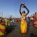An Indian devotee prays the Sun God as others take holy dips at Sangam, the confluence of the Rivers Ganges, Yamuna and mythical Saraswati on Maghi Purnima or the full-moon day, considered an auspicious bathing day, during the Maha Kumbh festival in Allahabad, India. Millions of Hindu pilgrims have been attending the Maha Kumbh festival, which is one of the world's largest religious gatherings that lasts 55 days and falls every 12 years. (AP Photo/Rajesh Kumar Singh)