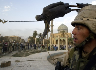 Iraqi civilians and U.S. soldiers pull down a statue of Saddam Hussein in downtown Baghdad after the US/British invasion in 2003.